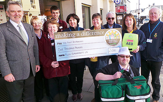 Smiling people hold large cheque for £1,000 made out to First Responders from Filco Supermarkets