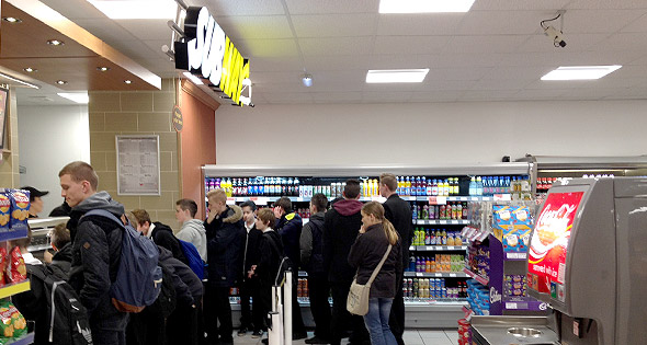 Customers queue at a Subway counter inside a Spar store.