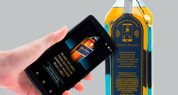 Person tapping smartphone against Johnnie Walker bottle