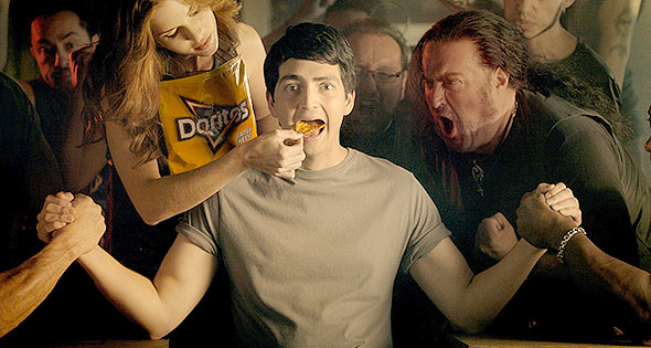 Man arm-wrestling two people simultaneously whilst being fed Doritos
