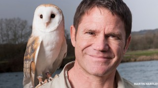 Steve Backshall with owl perched on his shoulder