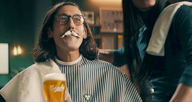 Man in barber's shop clutching pint of Carlsberg lager