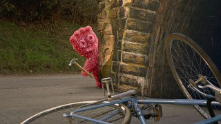 Maynards Sour Patch Kid brandishing a hammer next to an upturned bicycle