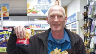Customer holds free cheese and onion slice