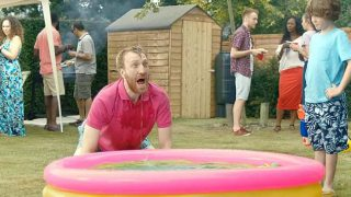 Man dipping head in paddling pool