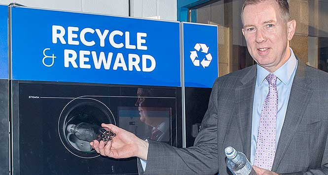 John Brodie feeds reverse vending machine