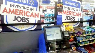 Self-scanning checkout with 'Walmart: investing in American jobs' sign